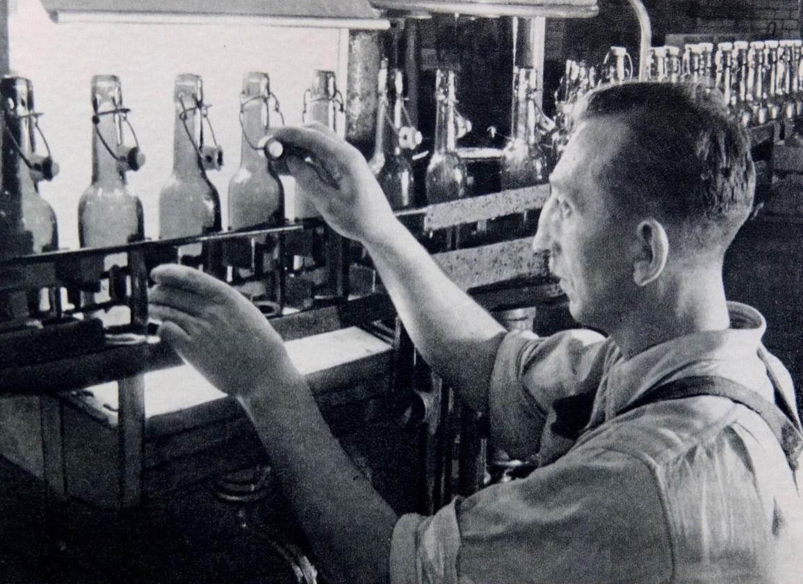 Flaschen-Spülapparat in der Bötzow-Brauerei Berlin, historische Aufnahme, Mann prüft gespülte Bierflaschen mit Schnappverschluss