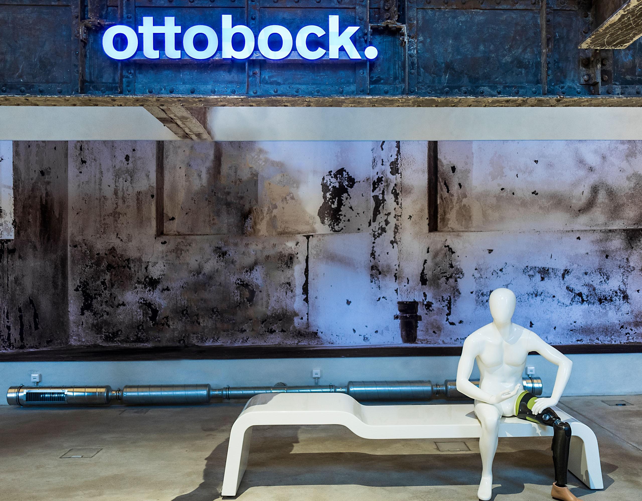 """Weiße Skulptur mit Beinprothese auf einer Bank vor bläulichem Hintergrund mit Leuchtschrift """"Ottobock"""""""