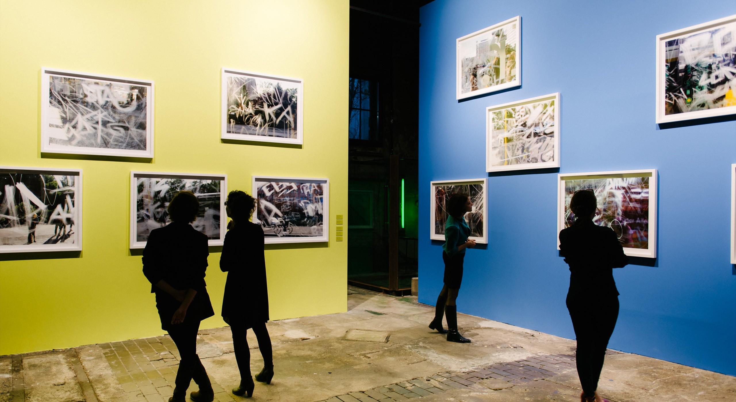 """Im Atelierhaus auf Bötzow – Menschen betrachten Werke der Ausstellung """"Scratches auf Bötzow"""""""
