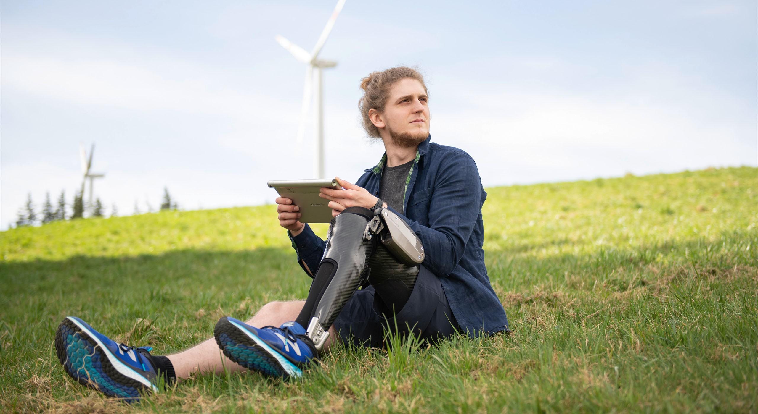 Mann mit Beinprothese sitzt auf Wiese und schaut in die Ferne