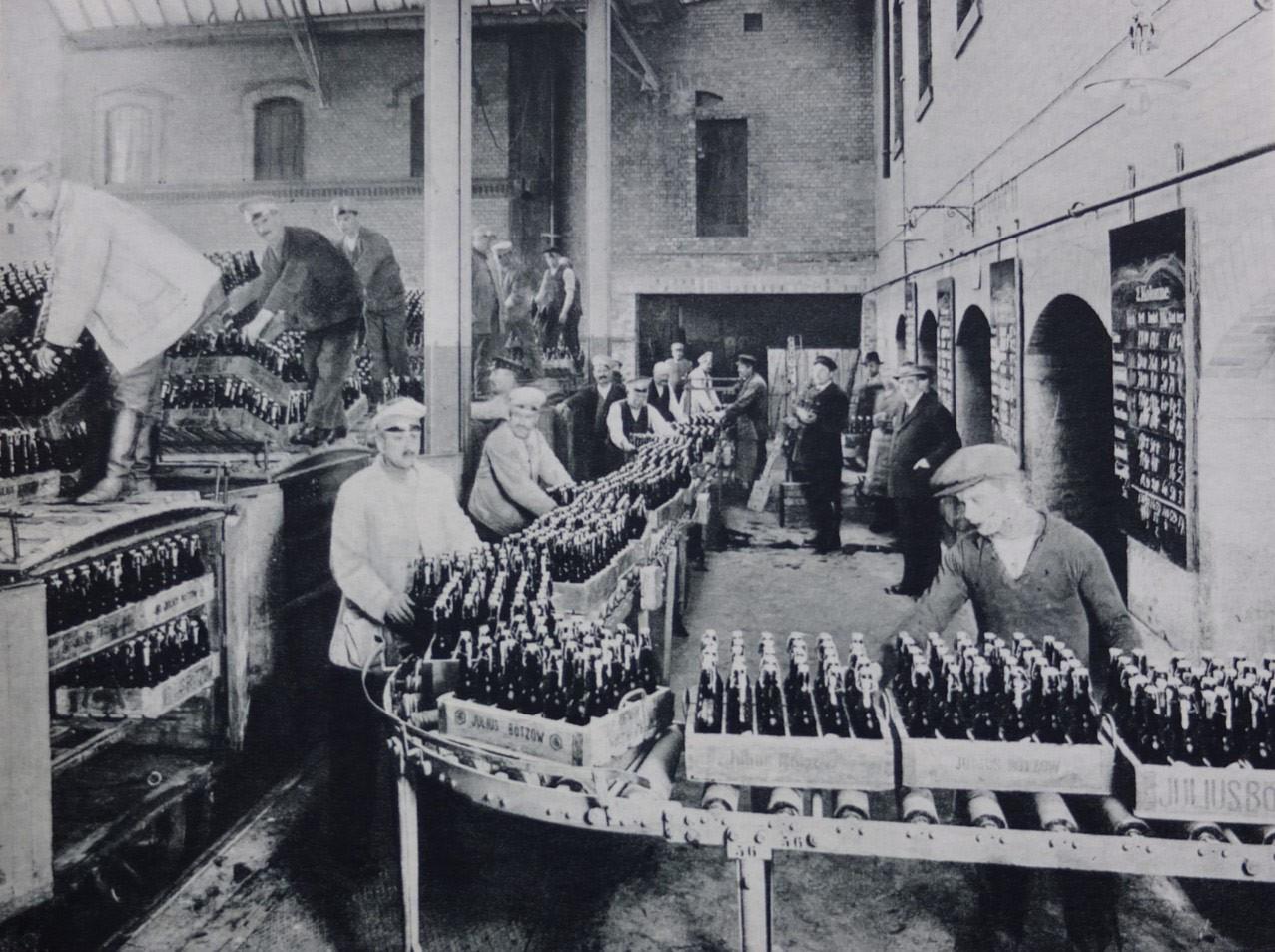 Arbeiter an der Produktionsstrecke der ehemaligen Bötzow-Brauerei Berlin, Flaschenkästen auf der Rollbahn